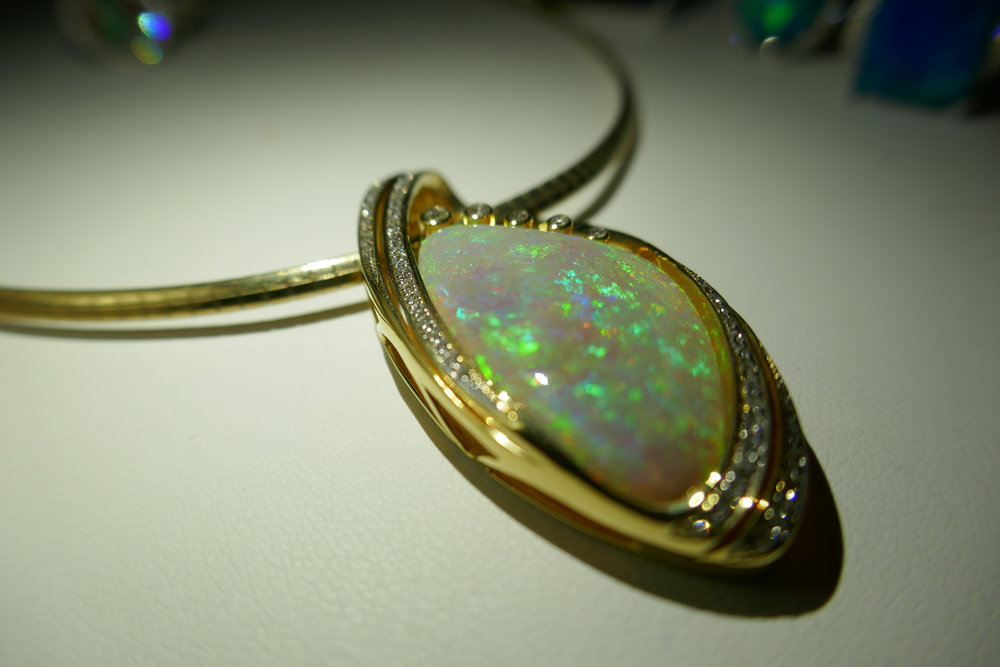 WHite opal - Light Opal is generally all one material, as opposed to Boulder or Black which tend to be two clearly definable materials fused together. It can be oval or free-form and often is of a calibrated size. It typically has a good cabochon. Light opal is mined mostly from Coober Pedy though some comes from Andamooka and Mintabie. Mintabie opal can come with a similar look to Black opal though usually has a telltale quality to the colour. Light opal is often used for doublets and triplets as it is easy to slice as it comes out of the ground in solid pieces(ie the whole rock is white opal)