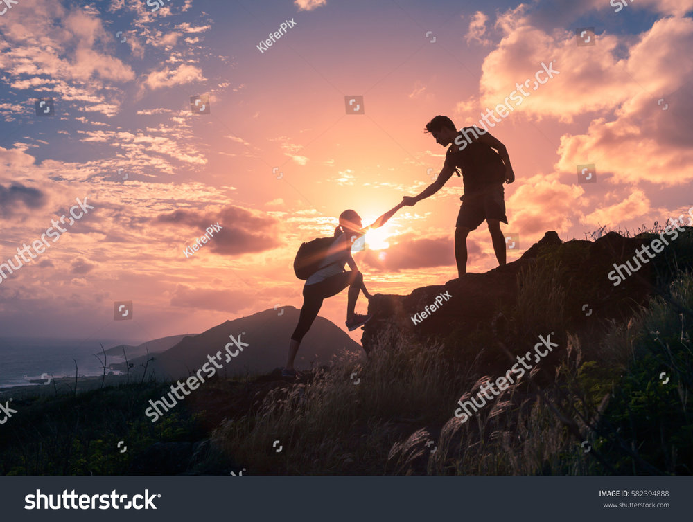 stock-photo-people-helping-each-other-hike-up-a-mountain-at-sunrise-giving-a-helping-hand-and-active-fit-582394888.jpg