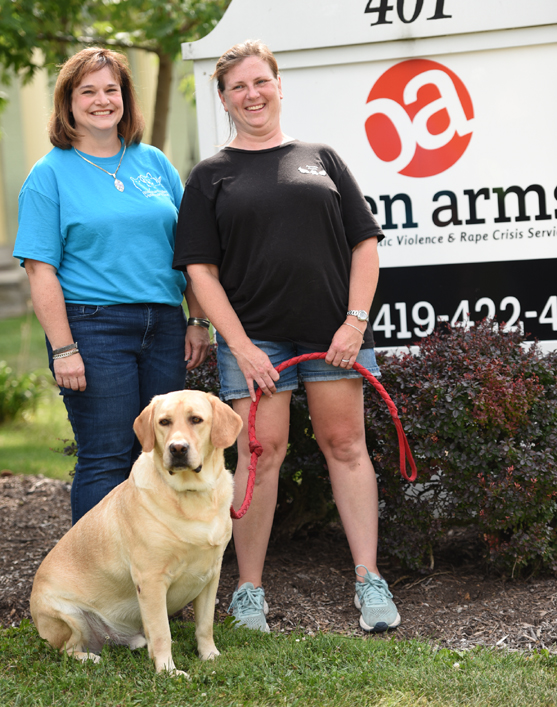 Veterinary social worker Joann Fuller, left, and Pawsible Angels CEO Michele Frank are shown with therapy dog Miles outside of Open Arms. A new partnership between Open Arms, Pawsible Angels, Blanchard Valley Veterinary Clinic and an anonymous animal advocate will allow for vet care and housing for pets of victims and families fleeing from domestic violence. (Photo by Randy Roberts)
