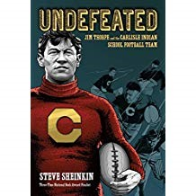 Undefeated: Jim Thorpe and the Carlisle Indian School Football Team  - Steve Sheinkin978-1-59643-954-2In Undefeated, Sheinkin captures the story of Jim Thorpe, one America's greatest athletes, in a fast-paced nonfiction book. Thorpe's personal story is contrasted with the story of Pop Warner, his irascible coach who lives on in the history books as one of the winningest coaches ever. This narrative non-fiction book weaves the retelling of footballs' violent beginnings with the recounting of the Carlisle Indian School, where thousands of Native American children were shipped across country in a dark attempt to eradicate their culture. This page-turner of a book will appeal to anyone who loves to root for the underdog—both on and off the field.