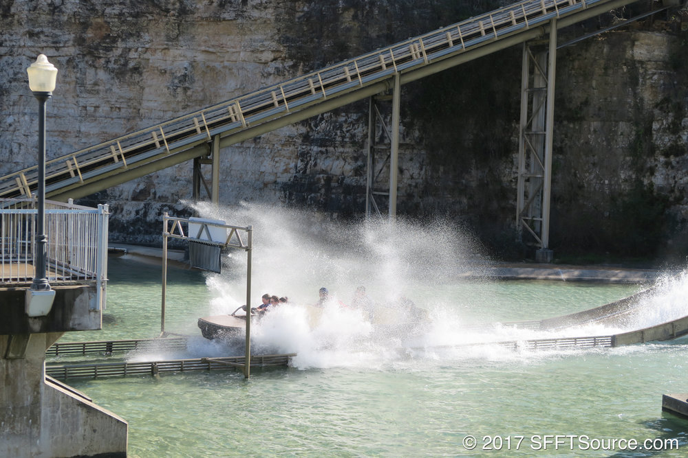 A boat splashes down at the bottom of Power Surge's drop.