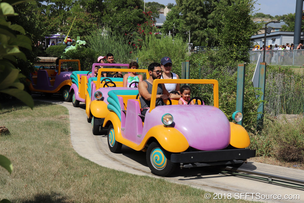 Guests climb aboard purple and yellow cars for a low-thrill adventure.