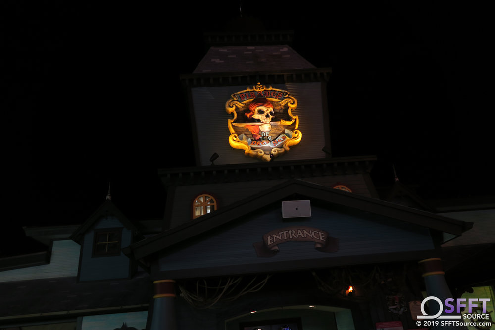 The Pirates of the Deep Sea sign illuminated at night.
