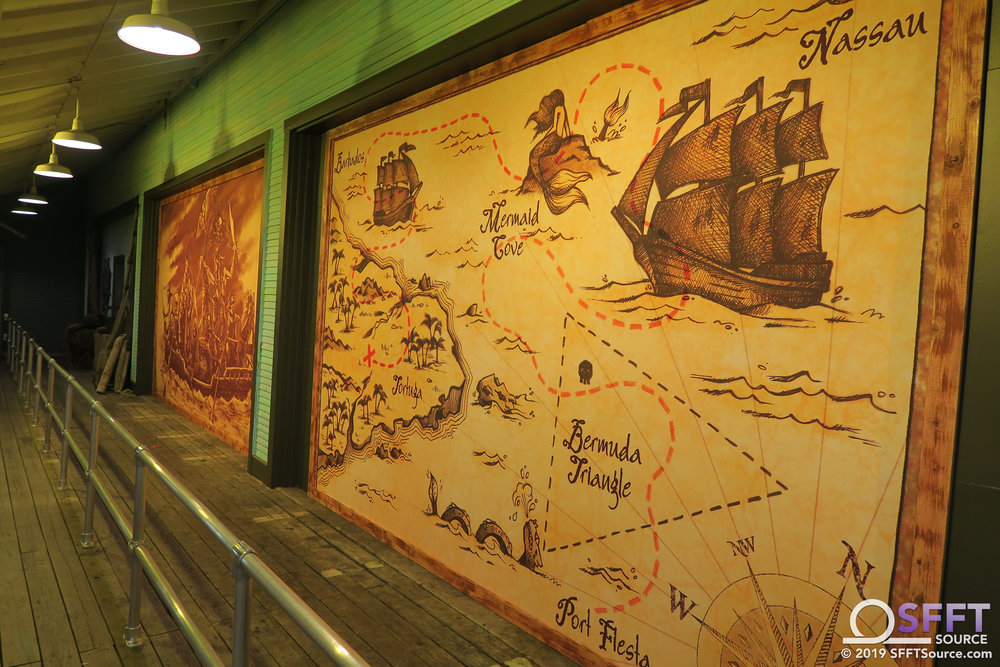 The outdoor portion of the Pirates of the Deep Sea queue features a large ride map and other decor.