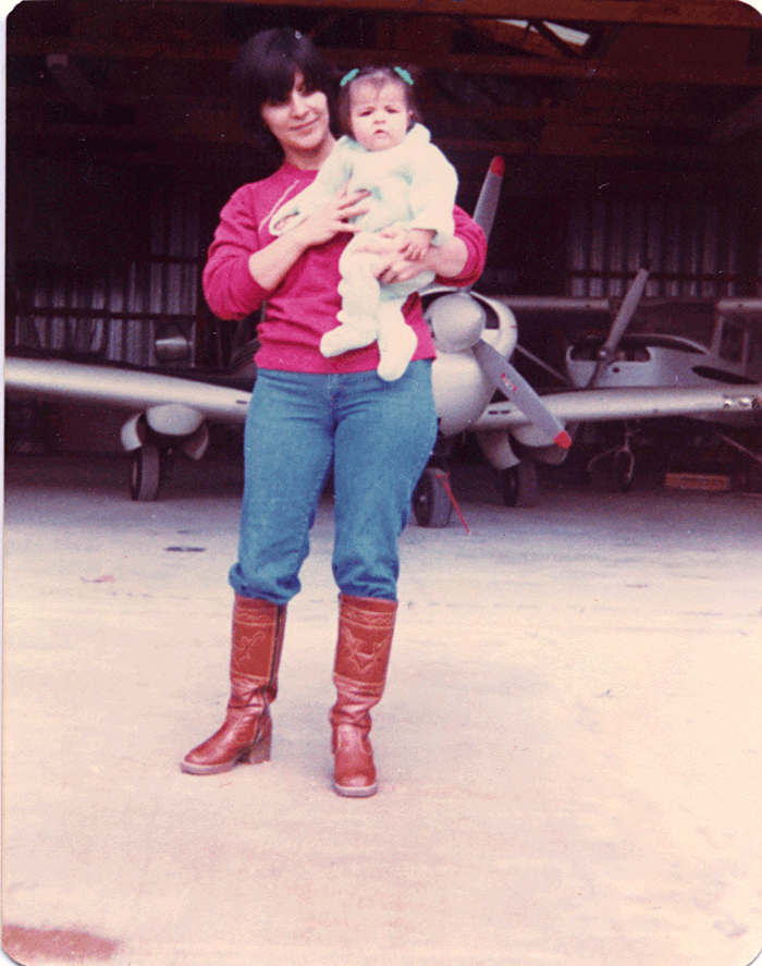 small_Mom---1979---with-Vita-and-airplane---600-dpi.png
