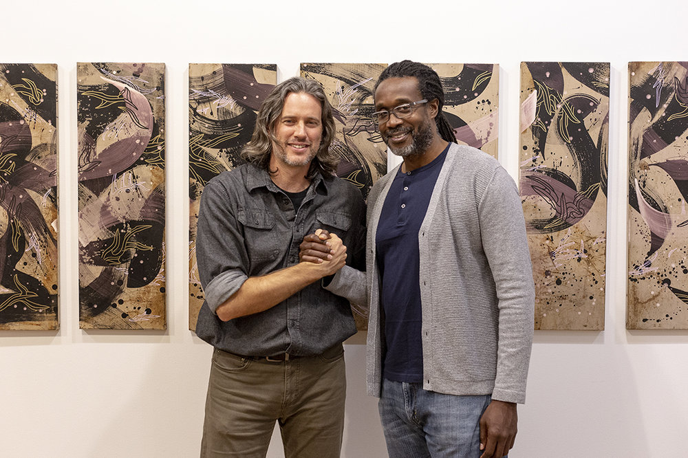 "Lowder (L) and KOOR (R) pictured in front of Kool Koor's artwork titled ""Miles' Tones"""