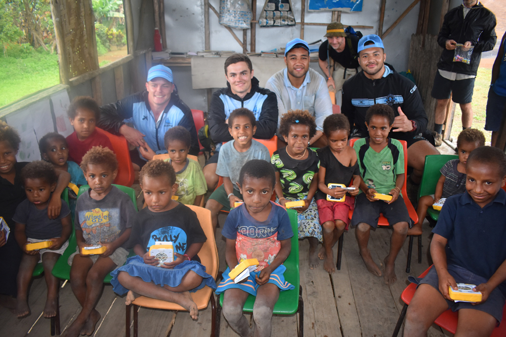 Members of the Crunulla Sharks Rugby team distributing SolarBuddy lights to Efogi School in PNG with CEO Simon Doble.