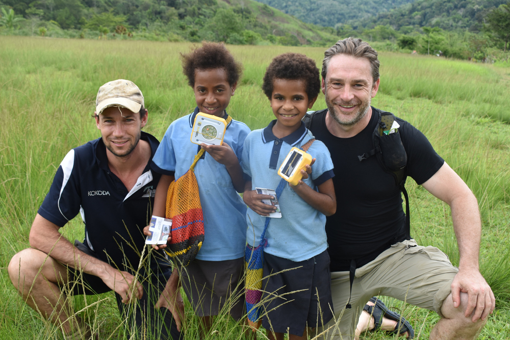 CEO, Simon Doble with On Track Expeditions and two excited students of Manai Community School receiving their SolarBuddy lights.