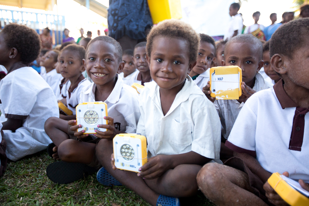 Students in PNG proudly showing off their new SolarBuddy lights.