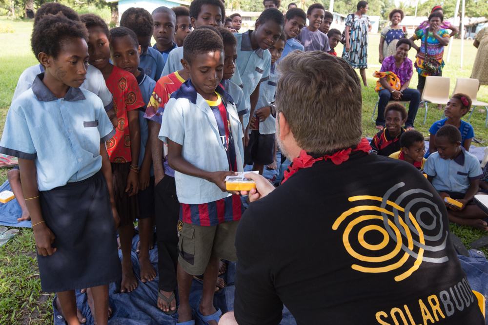 Simon giving children in the Kupiano region, PNG, SolarBuddy lights.