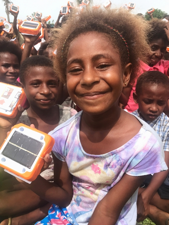 Students in PNG receiving their SolarBuddy lights.