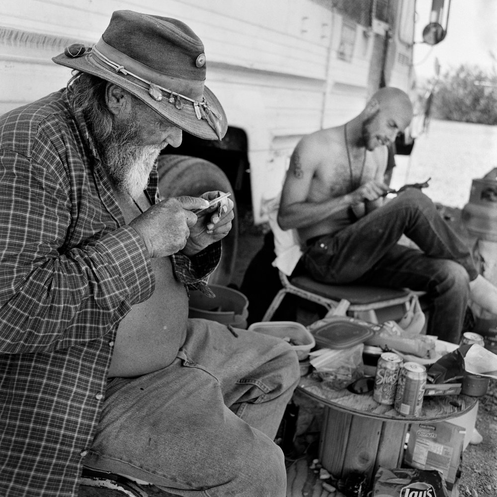 "Hornfeather makes a living carving jewelry from horn and bone that he finds, and trains apprentices such as Sideshow Mike (right). Of his lifestyle, Hornfeather says, ""we're travelers, not homeless."""