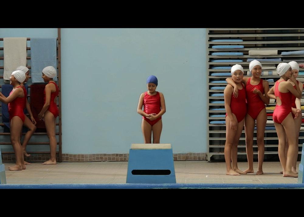 AURORA - Anais DelgadoQuito / 2017 / 10minVIER 8 / CINE UNIVERSITARIO / 17h00SAB 9 / FLACSO CINE / 20h00Aurora es una niña de 12 años que se encuentra en clases de natación con un dolor constante en el estómago. El entrenador de la clase pide a las niñas lanzarse una a una en un chapuzón al agua. Con mucho miedo que llegue su turno, Aurora, al intentar esconderse de toda presión y su incomodidad en el cuerpo, cae por accidente a la piscina sin saber que ésta la sumergirá en una metamorfosis a la adultez. Con el cambio en su cuerpo de niña a mujer, Aurora tendrá que salir de la piscina y así enfrentarse a otro tipo de miradas de la sociedad a la que no estaba acostumbrada cuando era niña.