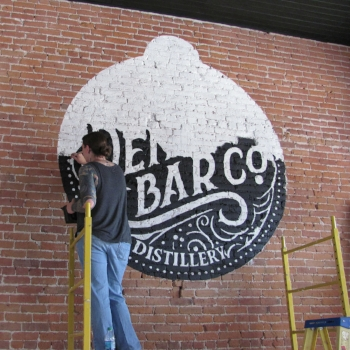 Mimi painting the Denny Bar Co. logo on their wall.
