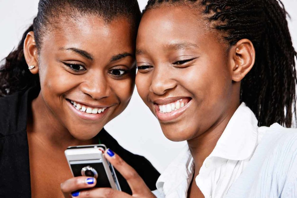 Two-beautiful-women-look-at-cellphone-screen-smiling-M.jpg