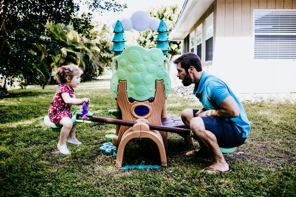 Father and daughter play on Seesaw in South Florida backyard