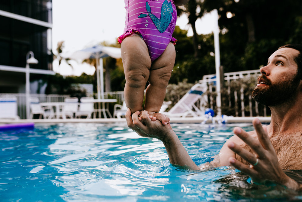 Dad balances daughter with one hand in pool on Sanibel island in Florida