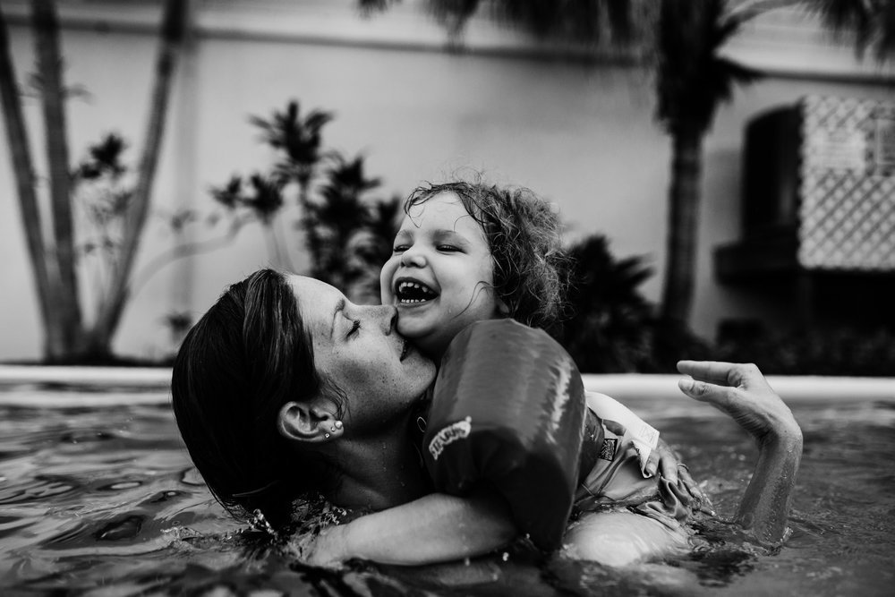 Mother holds daughter in pool while the little girl laughs
