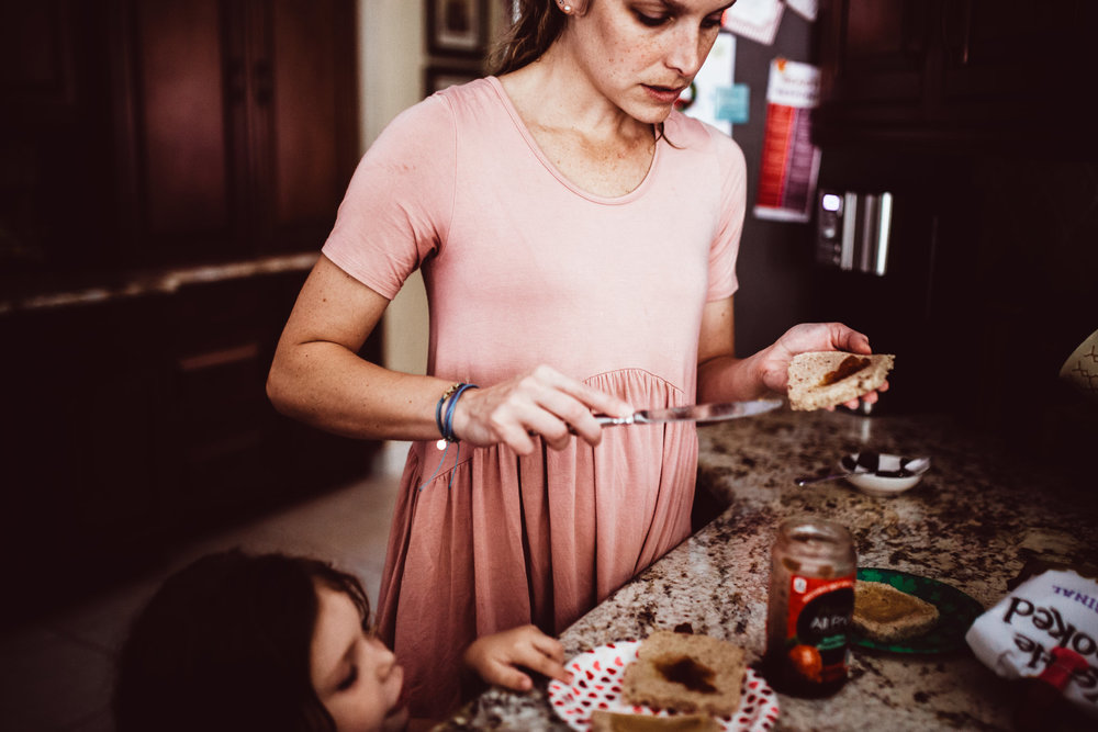Mom prepares peanut butter and jelly sandwich while daughter watches