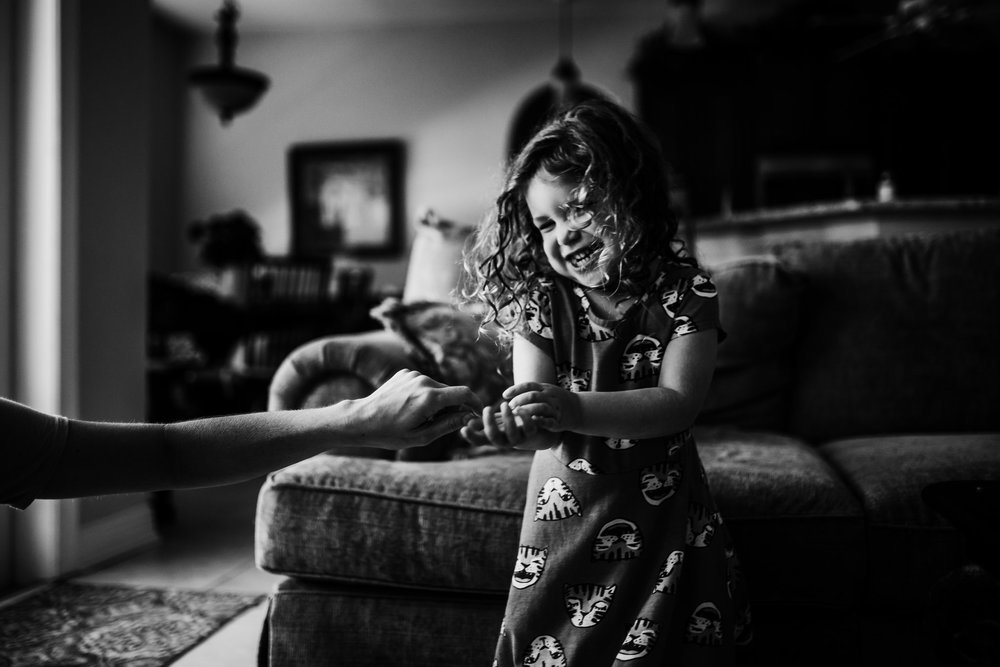 Little girl with curly hair laughs as mother tries to play with her