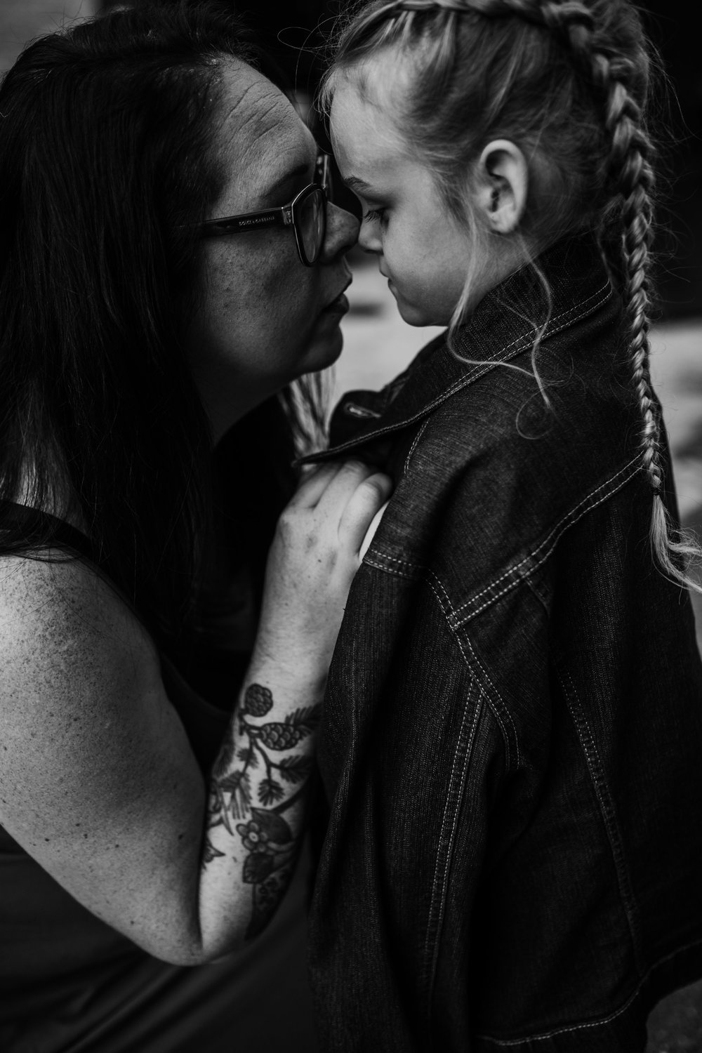 Daughter wears mom's oversized jean jacket as they share a sweet moment