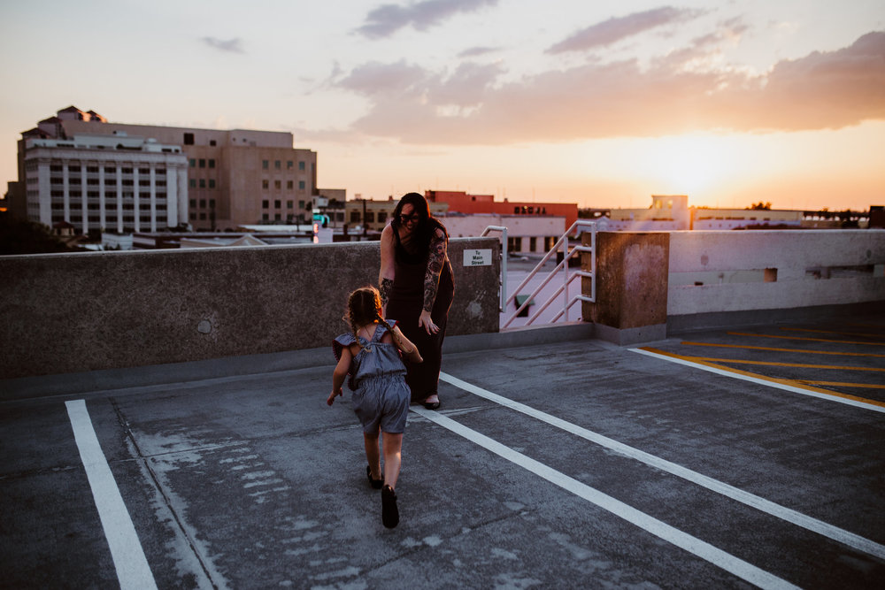 Daughter runs into mother's arms on roof with a sunset in the background