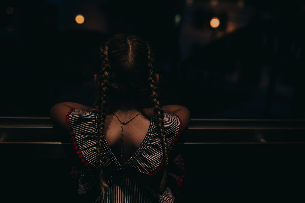 Little girl with pig tail braids looks outside glass elevator