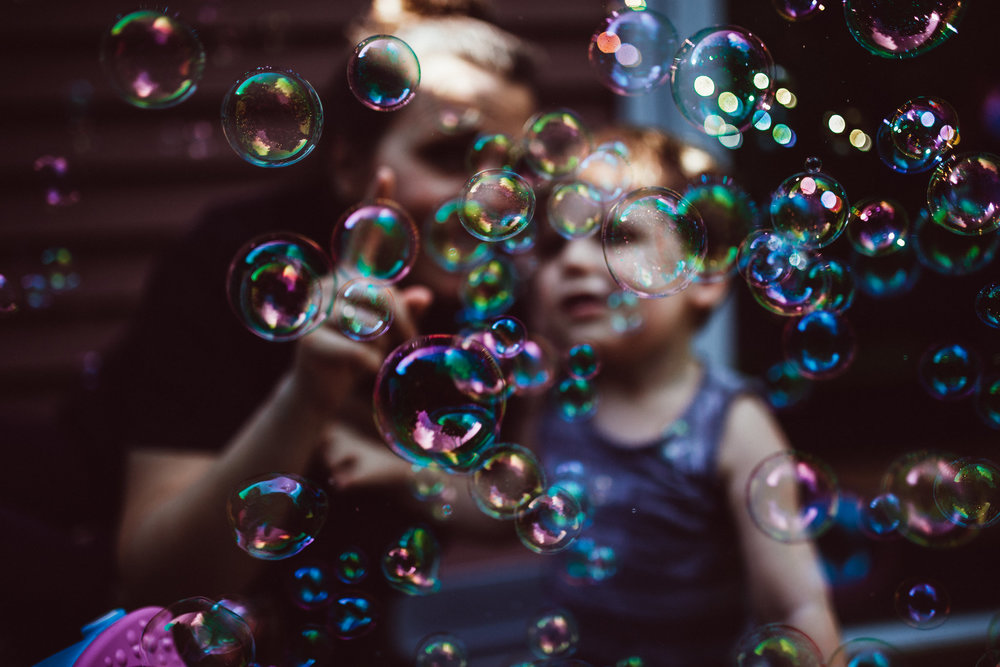 Mom and toddler behind a wall of bubbles