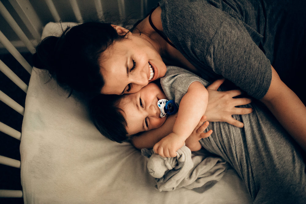 Mother and son cuddle in crib