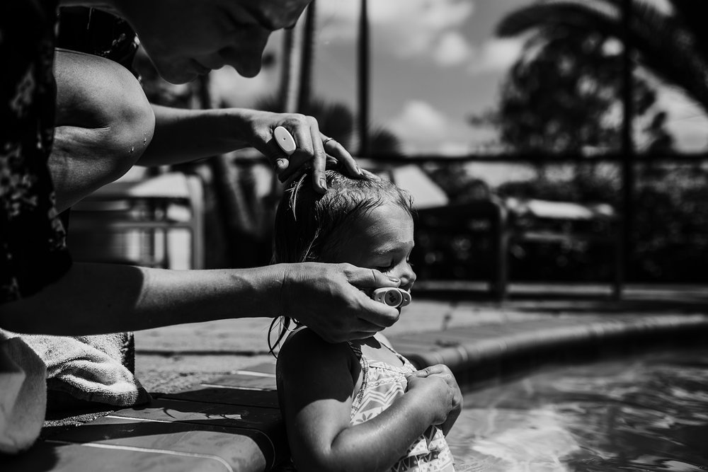 mother puts sunblock on toddler's face
