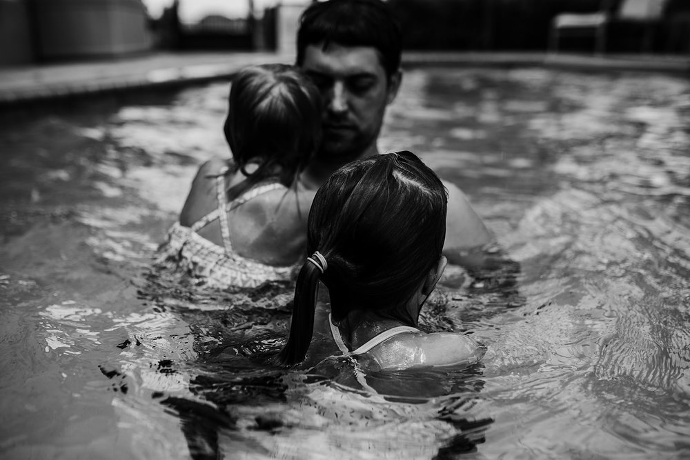 two little girls stay close to father in the pool