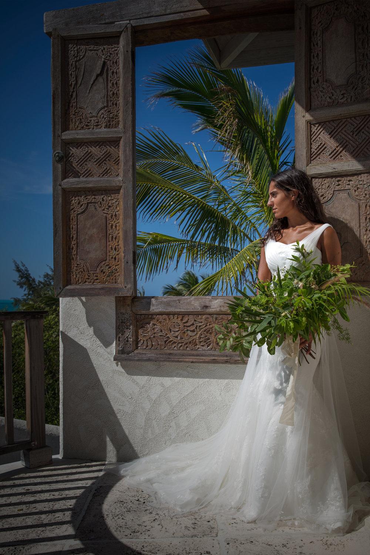 destination wedding summer resort wedding simple elegant wedding dress and green bouquet