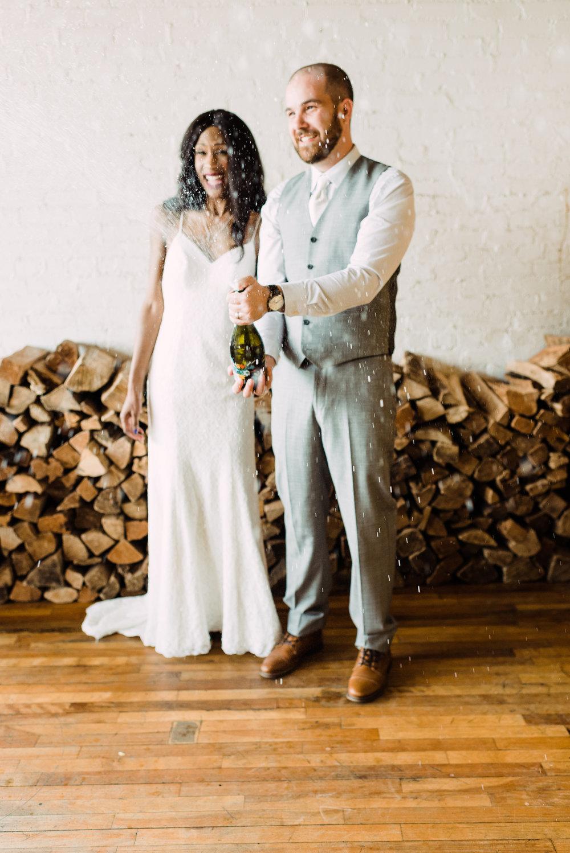 wedding photography champagne bottle popping moment modern wedding dress rustic wedding venue