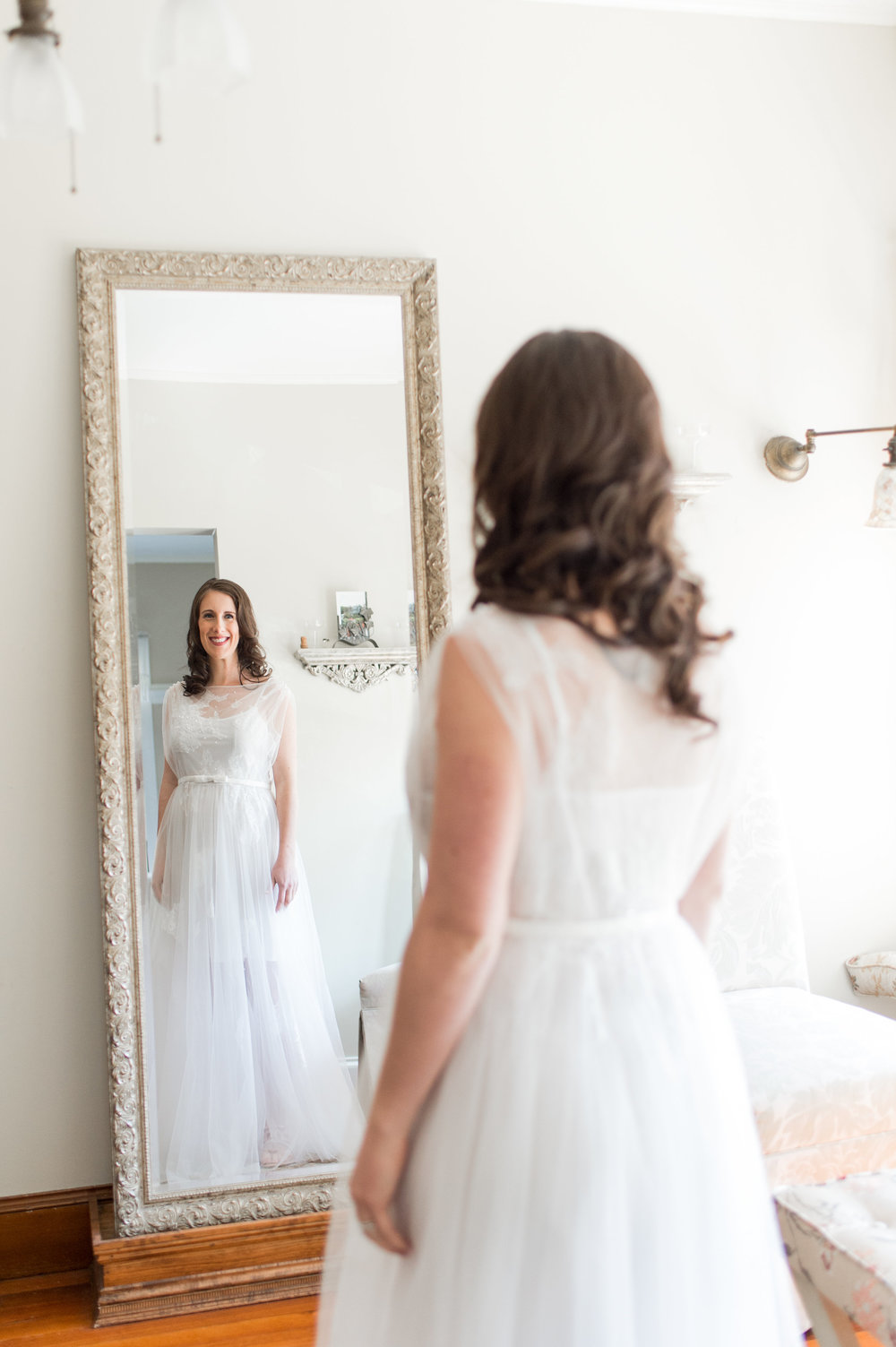 bride looking at herself in mirror unique two piece wedding dress