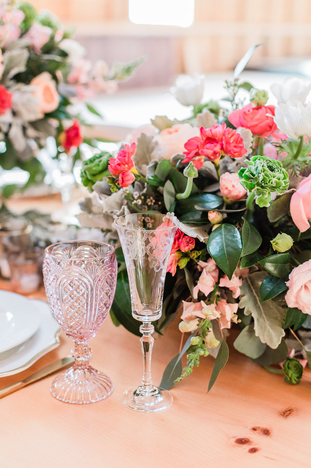 warm tone floral decorations and table setting pink colored glass indoors