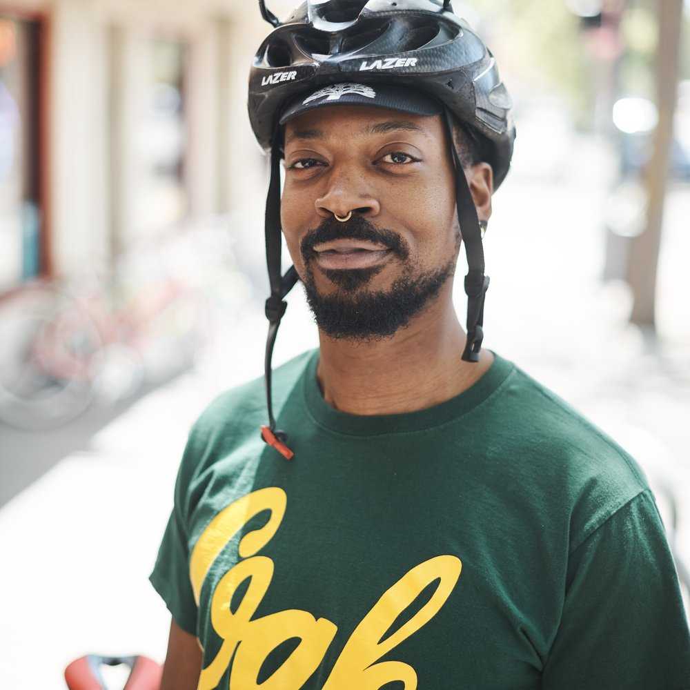 "Benton Williams   Benton is a first-year mechanic from Oakland, Calif. 13 years ago, he found himself without a car, and started cycling as a way to get around. Soon, he was building bikes and doing repairs for friends. Currently, he has five bikes, but his favorite is a Litespeed TI road bike that he built up to be ""as fast as possible"". As a super tall guy, Benton has a hard time finding bikes that fit. He loves to find old frames and build them into road bikes."