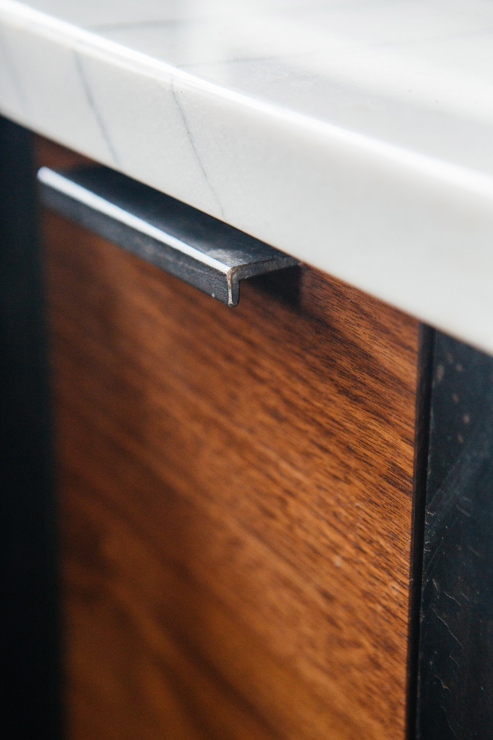 Detail of walnut cabinet with custom steel hardware