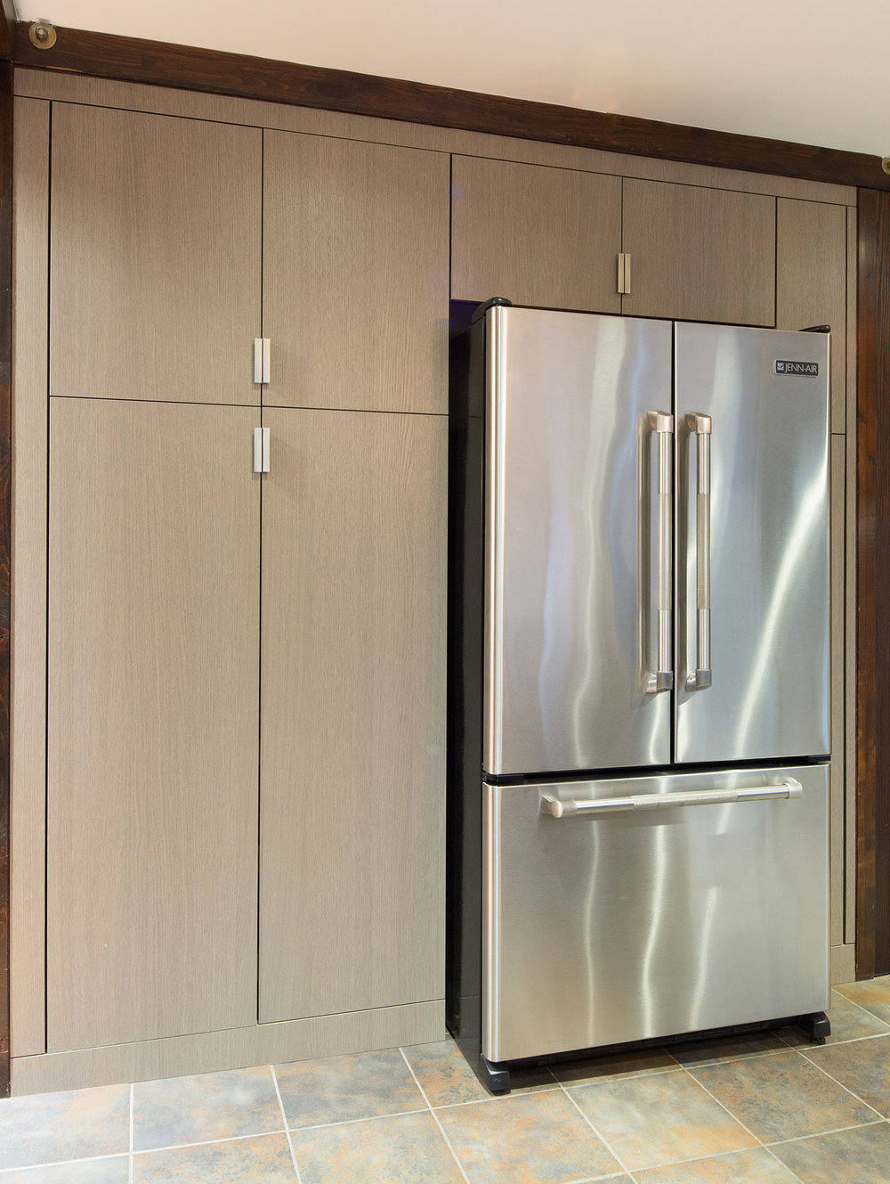 Custom kitchen cabinetry surrounding a refrigerator in grey oak Shinoki
