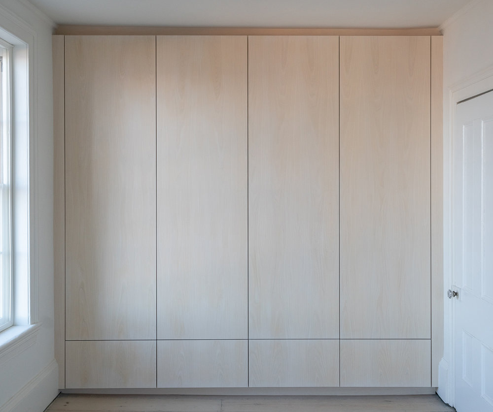 Custom built-in bedroom closet in whitewashed ash