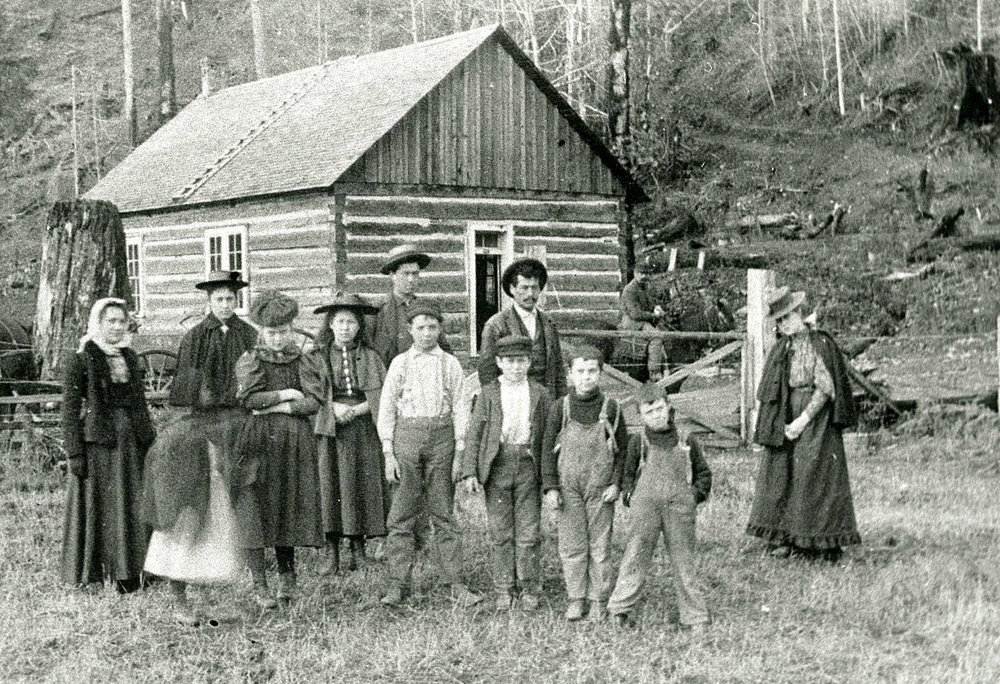 A group of unidentified adults and children stand in front of a log building in the Brinnon area in the 1890s. (Jefferson County Historial Society)