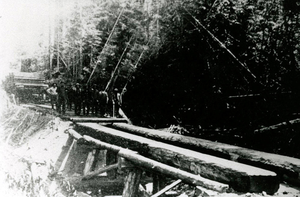 A Log bridge is shown near Brinnon in the 1890s. The loggers' identities are unknown. (Jefferson County Historical Society)