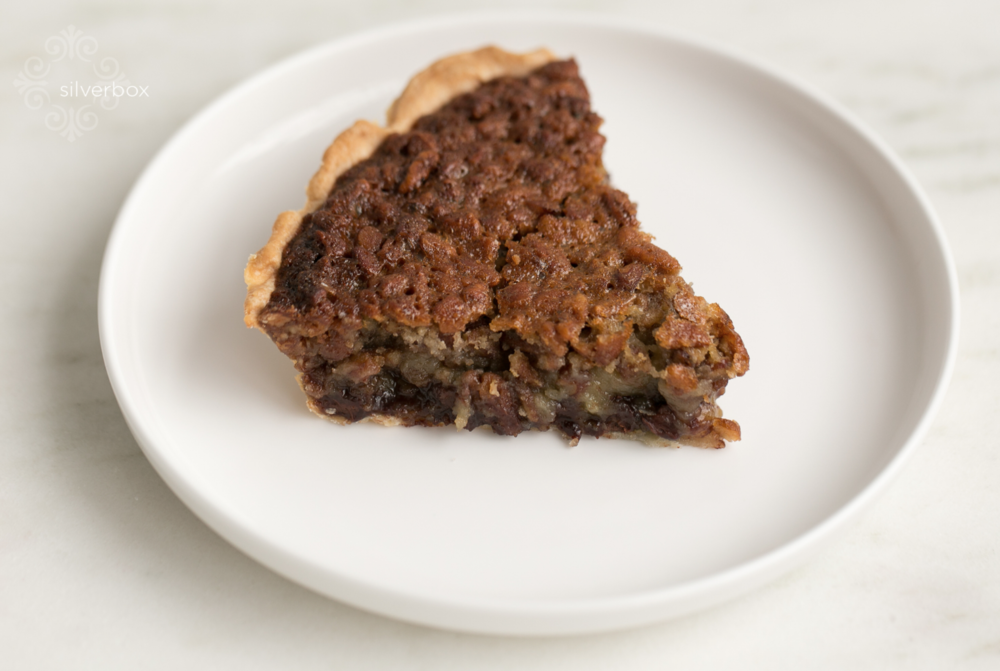 Chocolate Bourbon Pecan - With chocolate, bourbon, and pecan in one pie— what's not to love? The mix of a crunchy nut topping with a smooth chocolate center is enough to have you thinking about this pie months after your last bite. The hints of bourbon round out this decadent treat and move it from snack level to full-blown dessert. Drop by the shop and see for yourself!
