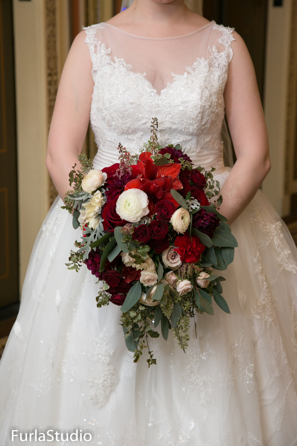 Gorgeous winter wedding bouquet with red, white and burgundy roses. Cascading bouquets are gorgeous in Chicago winter weddings | Your Day by MK | Chicago Wedding Planner | MK Andersen