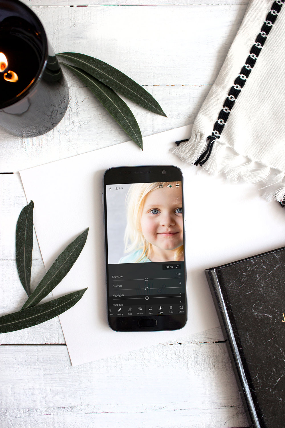 Photo shows a phone with Adobe Lightroom CC opened to editing screen. Lightroom is a great app for on-the-go-entrepreneurs like bloggers. It allows you to use presets and customize photos for your brand.
