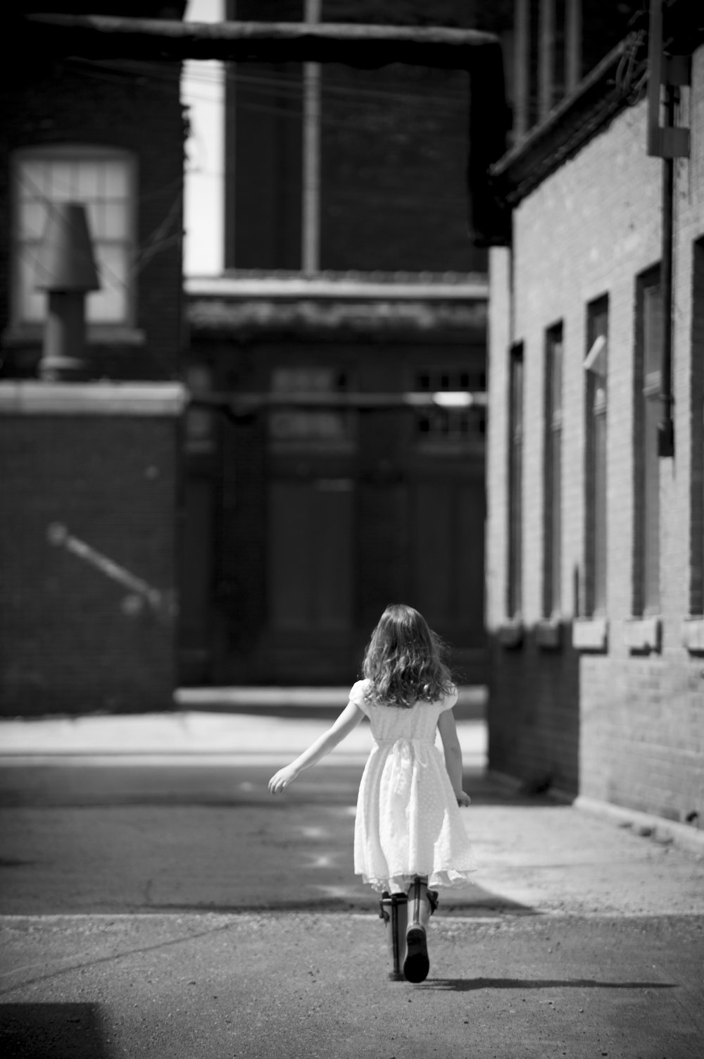 Marta-Hewson-Lifestyle-portrait-little-girl-walking-away-industrial.jpg