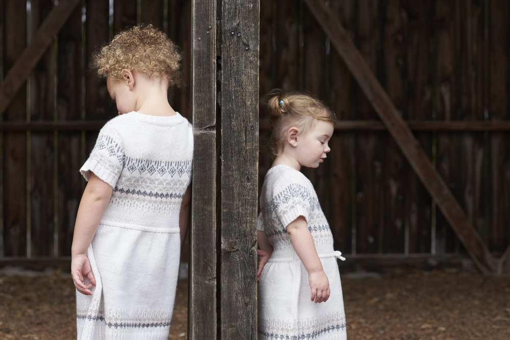 Marta-Hewson-Lifestyle-portrait-sisters-looking-away-barn-doors.jpg