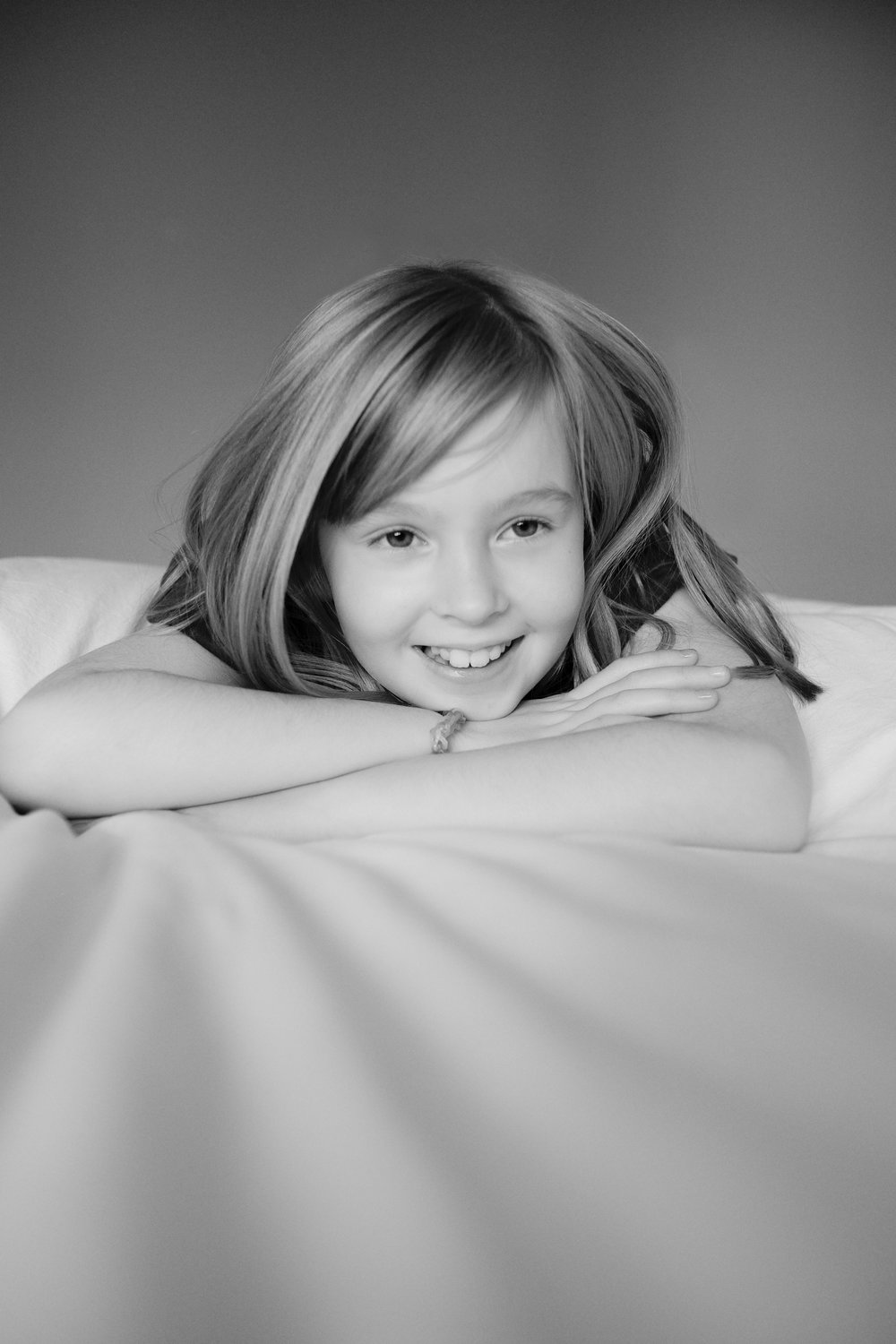 Marta-Hewson-Lifestyle-portrait-young-girl-smiling-on-bed.jpg