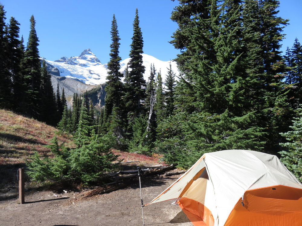 Outdoor dirt campsite with an orange tent surrounded by trees with a mountain in the background with snow on it