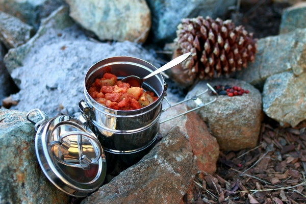 Steel cooking pot with food inside sitting on rocks outdoors