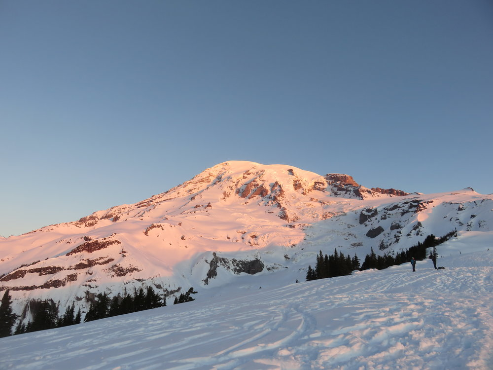 Snow covered mountain at sunrise against a blue sky